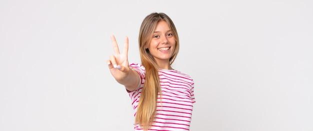 Ładna blondynka uśmiechnięta i wyglądająca na szczęśliwą, beztroską i pozytywną, gestykulującą zwycięstwo lub pokój jedną ręką