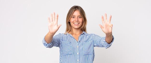 Ładna blondynka uśmiechnięta i wyglądająca przyjaźnie, pokazująca cyfrę dziesiątą lub dziesiątą z ręką do przodu, odliczając w dół