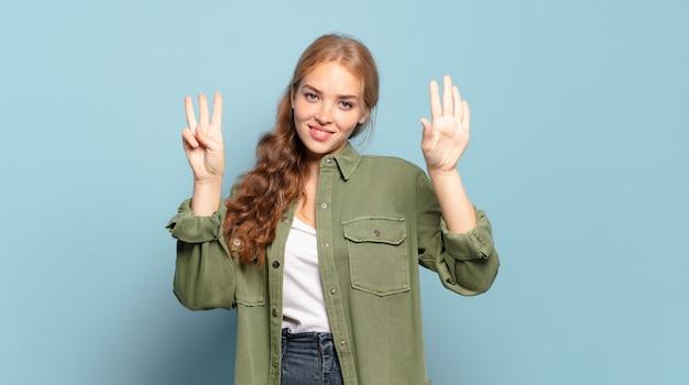 Ładna blondynka uśmiechnięta i wyglądająca przyjaźnie, pokazująca numer osiem lub ósmy z ręką do przodu, odliczający w dół
