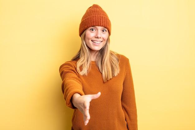 Ładna blondynka uśmiechnięta, wyglądająca na szczęśliwą, pewną siebie i przyjazną, oferująca uścisk dłoni w celu zawarcia umowy, współpracująca