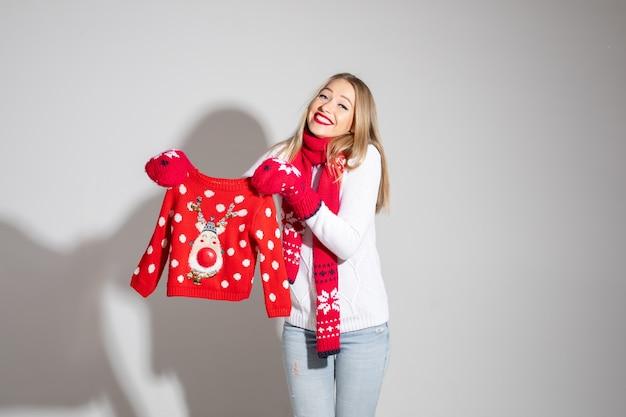 Ładna blondynka w biały sweter, czerwony szalik i rękawiczki trzymając piękny czerwony sweter dziecięcy z reniferem. prezent świąteczny dla dziecka.