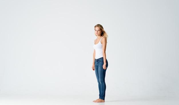 Ładna blondynka w dżinsach stoi boso na podłodze na białym tle modelki