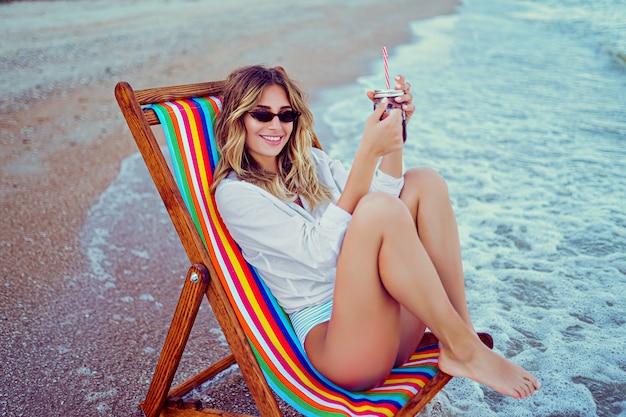 Ładna blondynka w kształcie sercowych okularów przeciwsłonecznych, białej koszuli i rozebranego stroju kąpielowego relaks na leżaku i drinków. koncepcja wakacji letnich