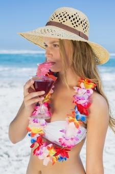 Ładna blondynka w kwiecistej girlandy popijania koktajlu na plaży