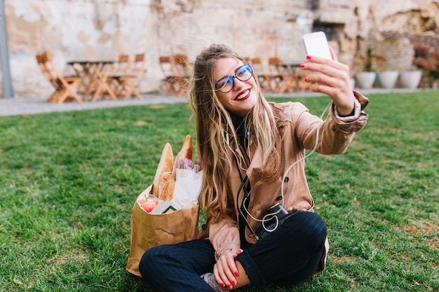 Ładna blondynka w okularach dokonywanie selfie ręką siedząc na zielonej trawie w parku. urocza młoda kobieta odpoczywa po zakupach i robieniu zdjęć do profilu instagram ze skrzyżowanymi nogami