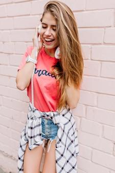 Ładna blondynka w różowej koszuli i niebieskich dżinsowych szortach słuchająca ulubionej muzyki w dużych białych słuchawkach z zamkniętymi oczami