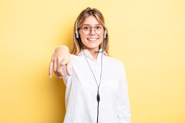 Ładna blondynka, wskazując na aparat wybierając ciebie. koncepcja zestawu słuchawkowego