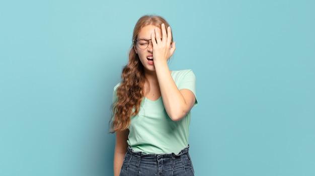 Ładna blondynka wygląda na zaspaną, znudzoną i ziewającą, z bólem głowy i jedną ręką zakrywającą połowę twarzy