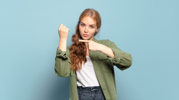 Ładna blondynka wyglądająca na niecierpliwą i wściekłą, wskazującą na zegarek, proszącą o punktualność, chce być punktualna