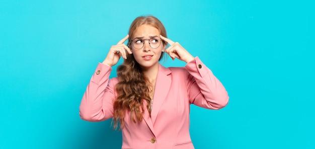 Ładna blondynka wyglądająca na skoncentrowaną i intensywnie zastanawiającą się nad pomysłem, wyobrażając sobie rozwiązanie wyzwania lub problemu