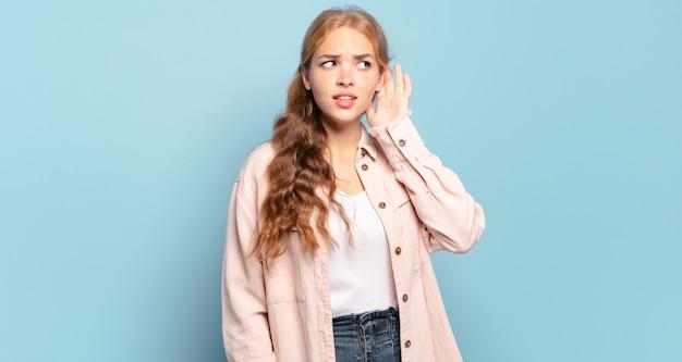 Ładna blondynka wyglądająca poważnie i zaciekawiona, słuchająca, próbująca usłyszeć tajną rozmowę lub plotkę, podsłuchująca