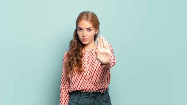 Ładna blondynka wyglądająca poważnie, surowo, niezadowolona i wściekła pokazuje otwartą dłoń wykonującą gest stop