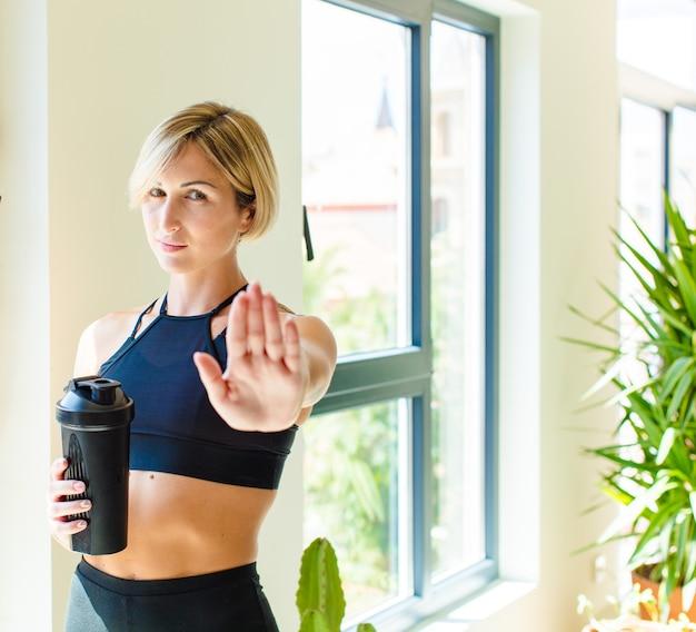 Ładna blondynka wyglądająca poważnie, surowo, niezadowolona i zła, pokazując otwartą dłoń wykonującą gest stop