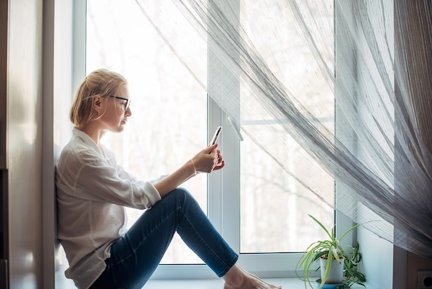 Ładna blondynka z bosymi stopami w okularach, dżinsach i białej koszuli, siedząc na parapecie w mieszkaniu, trzymając w ręku smartfon. relaksująca rozrywka w przytulnym wnętrzu domu. widok z boku, zbliżenie.