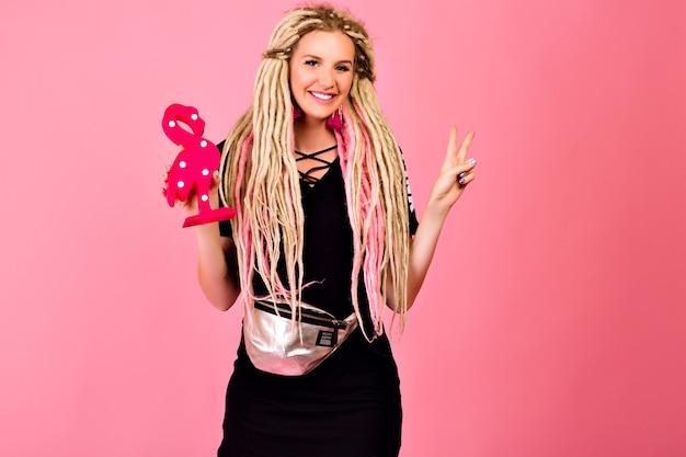 Ładna blondynka z długimi blond dredami trzymająca plastikowy flaming, ubrana w stylowy sportowy strój szykowny, zaskoczona emocjami, pop ostatnia stylizacja.