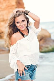 Ładna blondynka z długimi włosami pozuje do kamery na plaży, w pobliżu morza.
