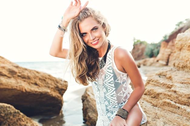 Ładna blondynka z długimi włosami siedzi na kamieniu na kamienistej plaży na tle zachodu słońca. ona uśmiecha się do kamery.