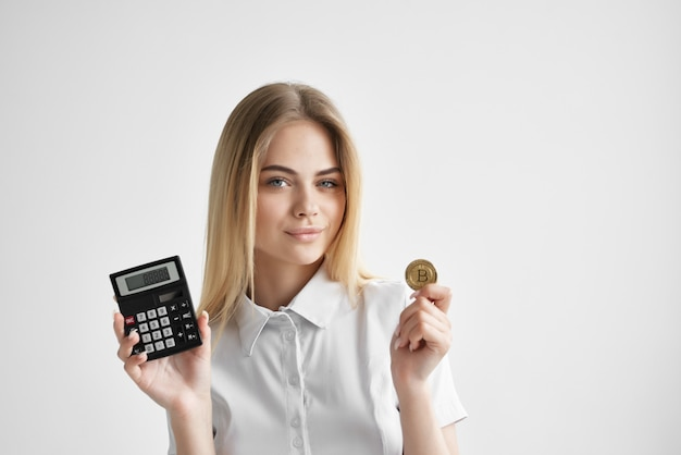 Ładna blondynka z kalkulatorem złota moneta kryptowaluta finansowa