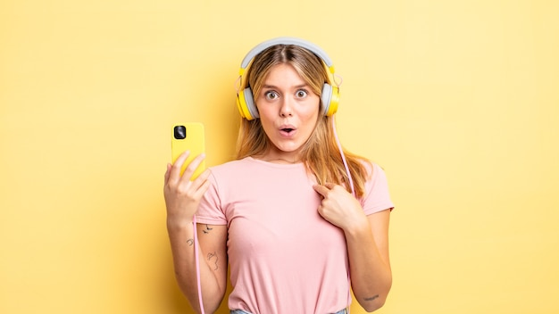 Ładna blondynka, zszokowana i zaskoczona, z szeroko otwartymi ustami, wskazując na siebie. koncepcja muzyki do słuchania
