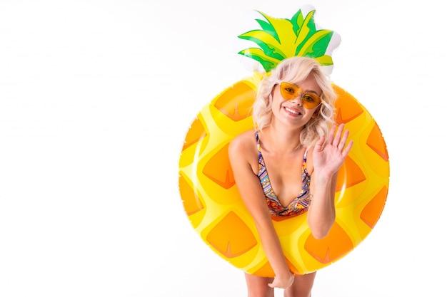 Ładna blondynki caucasian kobieta stoi w swimsuit z gumowym plażowym ananasa pierścionkiem i uśmiechami odizolowywającymi na bielu