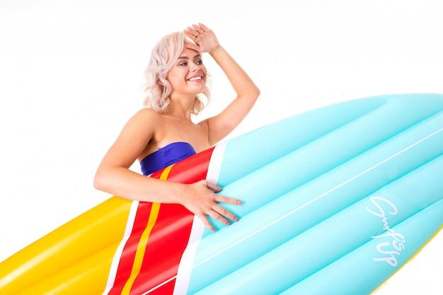 Ładna blondynki caucasian kobieta stoi w swimsuit z gumowym plażowym materac i ono uśmiecha się odizolowywającymi na bielu