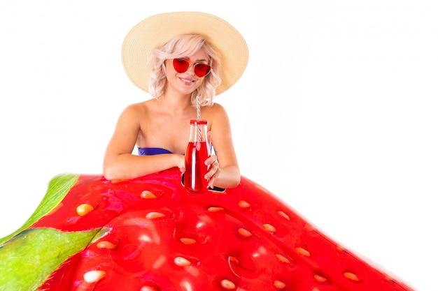 Ładna blondynki caucasian kobieta stoi w swimsuit z gumowym plażowym truskawkowym materacem, sokiem i uśmiechami odizolowywającymi na bielu