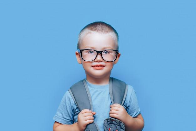Ładna blondynki chłopiec na błękitnym tle z plecakiem