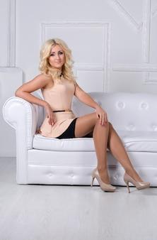 Ładna blondynki dziewczyna z jaskrawym makeup obsiadaniem na białym krześle