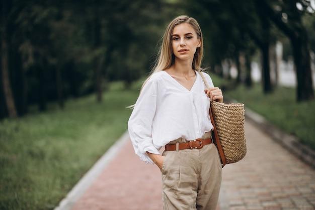 Ładna blondynki kobieta jest ubranym lata spojrzenie w parku