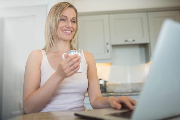 Ładna blondynki kobieta ma kawę i używa laptop