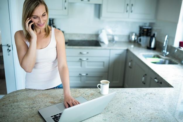 Ładna blondynki kobieta patrzeje laptop