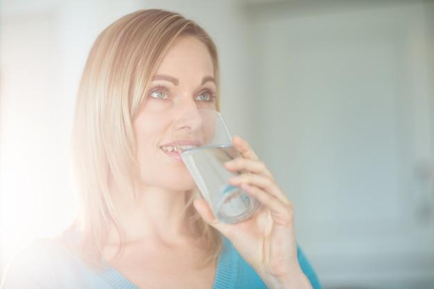 Ładna blondynki kobieta pije szkło woda