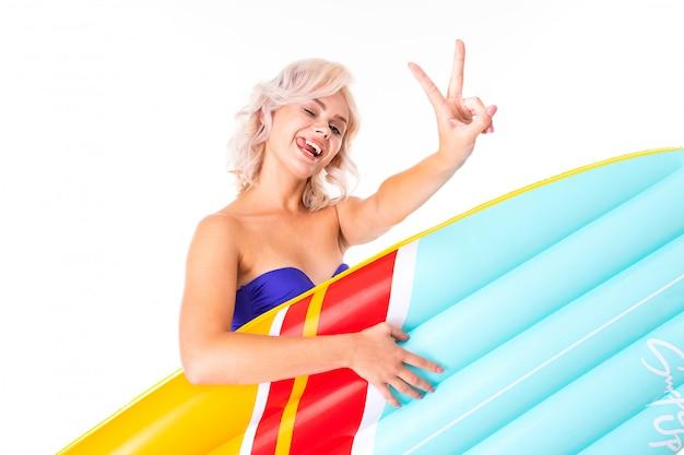 Ładna blondynki kobieta stoi w swimsuit z gumowym plażowym materacem, ono uśmiecha się i pokazuje pokój odizolowywającego na biel powierzchni