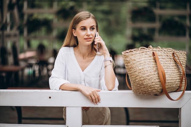 Ładna blondynki kobieta używa telefon outside w parku
