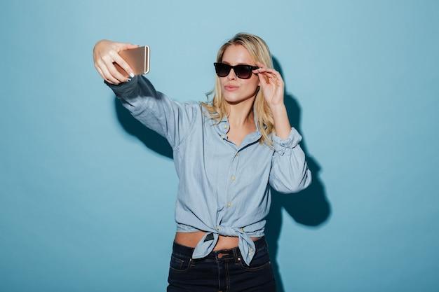 Ładna blondynki kobieta w koszula i okularach przeciwsłonecznych robi selfie na smartphone