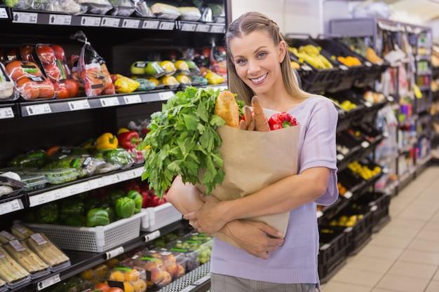 Ładna blondynki mienia torba z chlebem i warzywem
