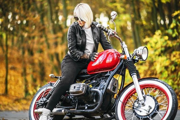 Ładna blondynki rowerzysty dziewczyna w okularach przeciwsłonecznych z czerwonym motocyklem na drodze w lesie