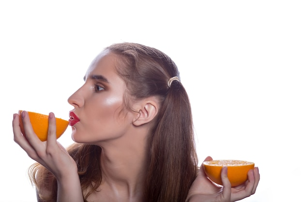 Ładna brunetka, bez koszuli, trzymająca kawałki pomarańczy w pobliżu ust, stojąca na białym tle