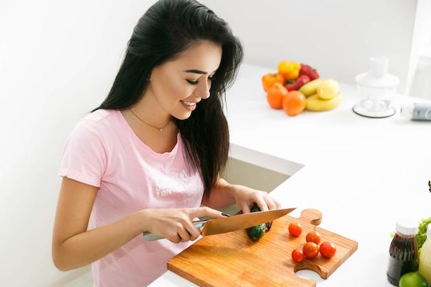 Ładna brunetka ciie warzywa na drewnianej desce w kuchni