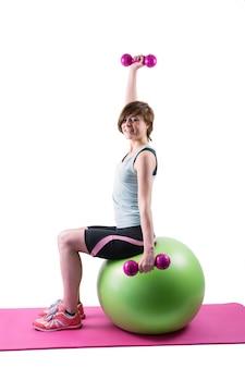 Ładna brunetka ćwiczy z dumbbells na sprawności fizycznej piłce