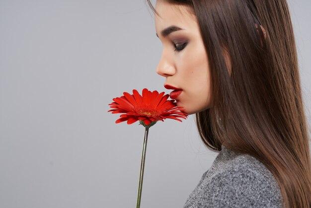 Ładna brunetka czerwony kwiat jasny makijaż studio szare tło