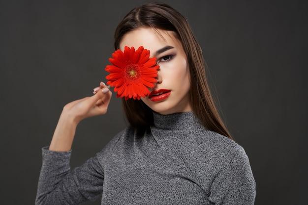 Ładna brunetka czerwony kwiat w pobliżu ciemnego tła makijażu twarzy. zdjęcie wysokiej jakości