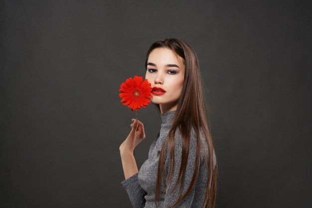 Ładna brunetka czerwony kwiat w pobliżu ciemnego tła makijażu twarzy