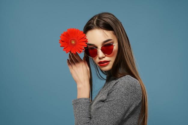 Ładna brunetka czerwony kwiat w pobliżu zbliżenie portretu twarzy