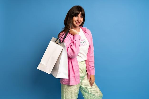 Ładna brunetka dama cieszyć się zakupami. stylowy wizerunek szczęśliwej kobiety