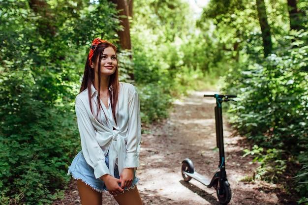 Ładna brunetka dziewczyna jeździ na hulajnodze elektrodowej w parku, w której ma na sobie białą koszulę. koncepcja ekologicznego transportu i wynajmu.