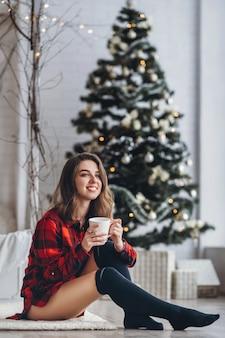 Ładna brunetka dziewczyna siedzi na podłodze w czerwonej koszuli i ciepłych skarpetkach z filiżanką kawy i choinką w tyle
