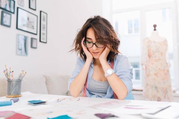 Ładna brunetka dziewczyna siedzi przy stole w pracowni. dziewczyna w niebieskiej koszuli jest zajęta oglądaniem szkiców w albumie.