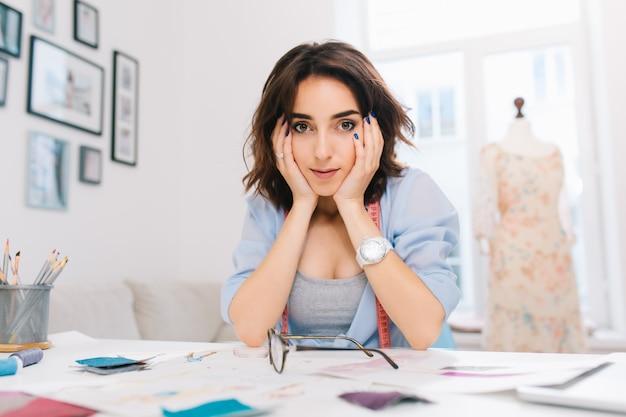 Ładna brunetka dziewczyna siedzi przy stole w pracowni. nosi niebieską koszulę i biały zegarek. wspiera twarz rękami i patrzy w kamerę.