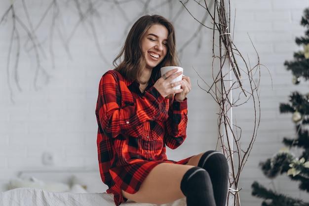 Ładna brunetka dziewczyna w łóżku na sobie czerwoną koszulę i ciepłe skarpetki z filiżanką kawy